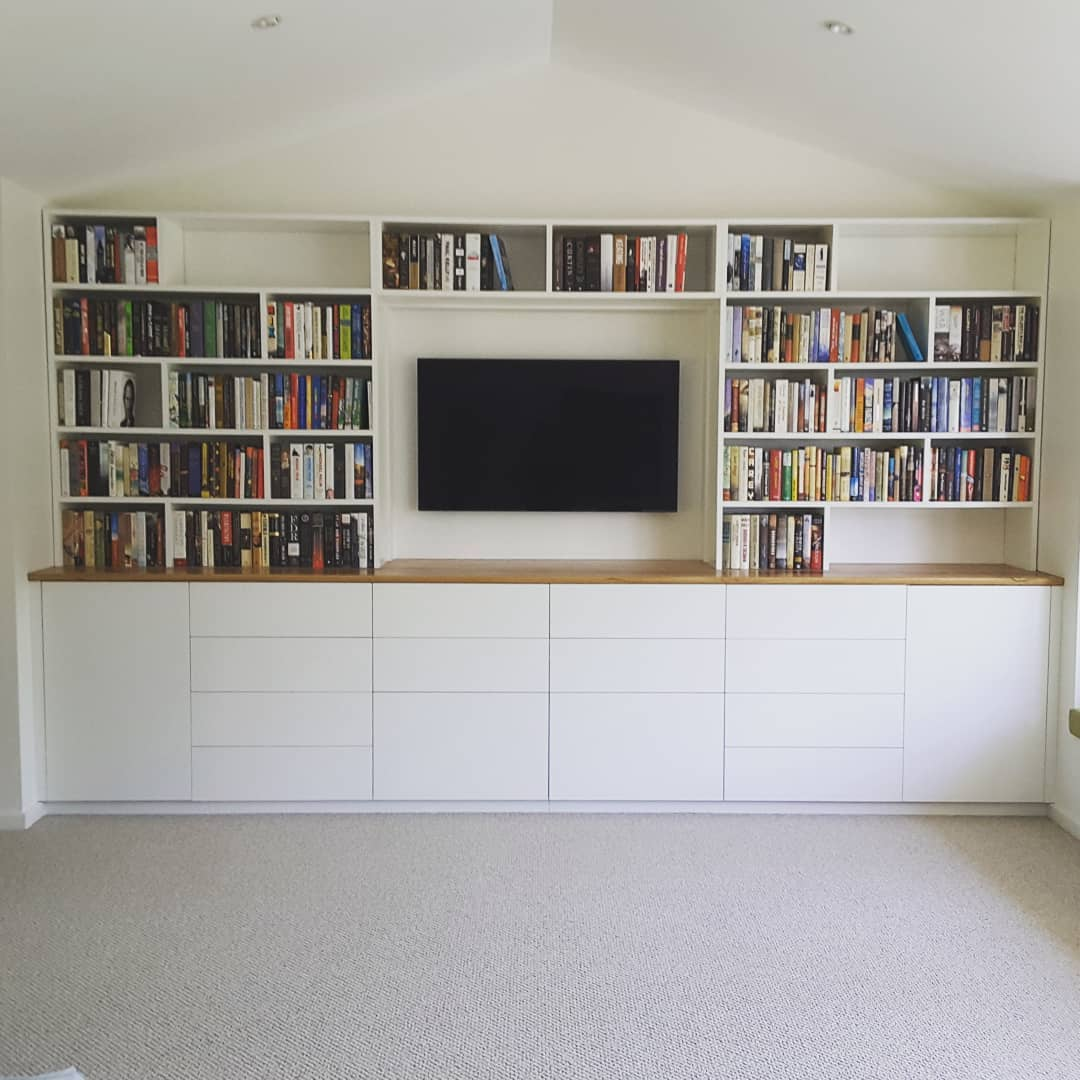 White timber entertainment unit with tv and surrounding bookshelves